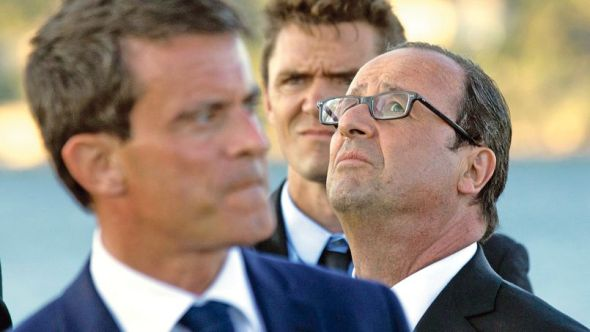 French President Hollande and Prime Minister Valls watch an air show at the end of the naval review aboard the Charles de Gaulle aircraft carrier
