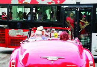 88345_un_autobus_de_transporte_p_ublico_pasa_por_una_calle_de_la_habana_mientras_turistas_pasean_en_un_clasico_carro_american_convertible_ap