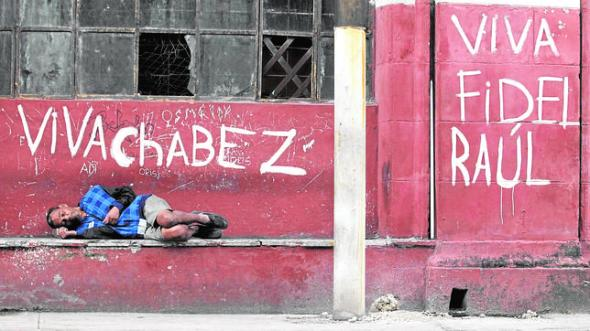 Man sleeps near graffiti in Havana