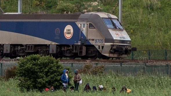TOPSHOTS Migrants are seen near a Channel Tunnel train in Coquelles near Calais, northern France, on late July 29, 2015. One man died Wednesday in a desperate attempt to reach England via the Channel Tunnel as overwhelmed authorities fought off hundreds of migrants, prompting France to beef up its police presence. AFP PHOTO / PHILIPPE HUGUEN
