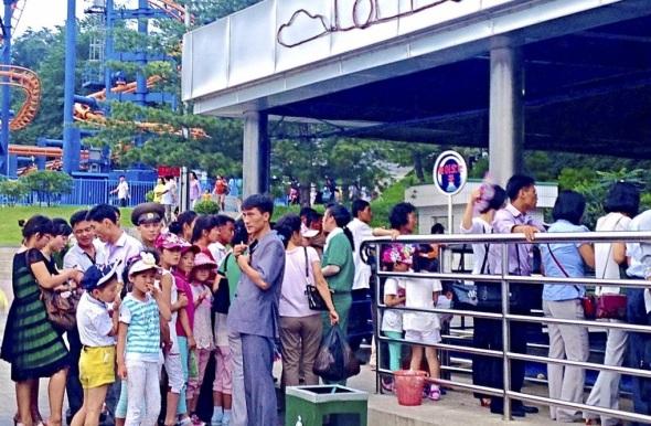 Ciudadanos de Pyongyang hacen cola para usar los coches de choque en el parque de atracciones.