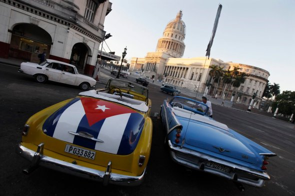Car with a Cuban flag is parked near Cuban Capitol in Havana