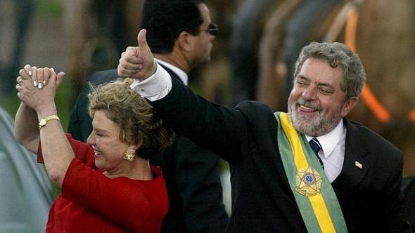 File photo of Brazil's then new president Lula da Silva gestures to thousands of followers as he rides past them with his wife, Marisa, after he received the presidential sash, in Brasilia