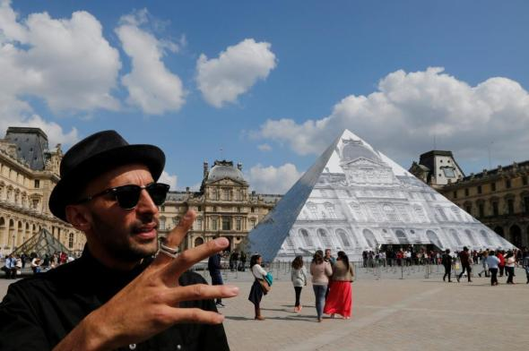 French artist JR stands in front of his lastest work, an image of the facade of Paris' Louvre covering the museum's famous pyramid entrance