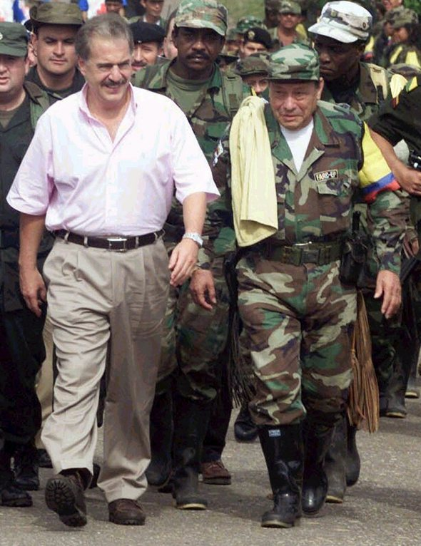 Colombian President Pastrana and Manuel Muralanda, leader of the rebel group Revolutionary Armed Forces of Colombia (FARC), walk before the start of a meeting in Los Pozos